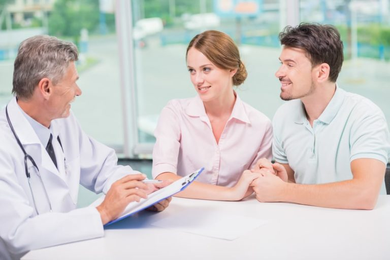 Family couple sitting in doctor's office at consultation