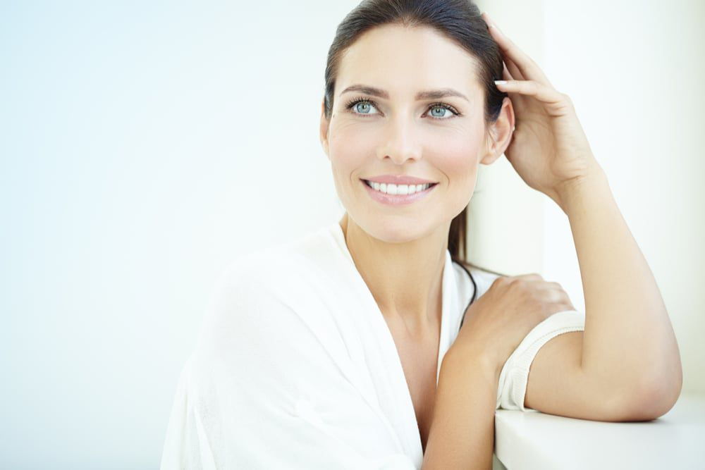 ZO Skin Health products Smiling 30 year old woman at the window. Fresh light blue background  skin care products